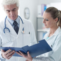 Confident doctor in the office checking medical records with his assistant, healthcare and teamwork concept